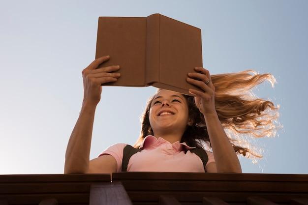 Souriant jeune livre de lecture blonde au soleil Photo gratuit