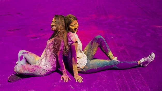 Souriant jeunes femmes assis dos à dos assis sur la poudre de couleur holi Photo gratuit
