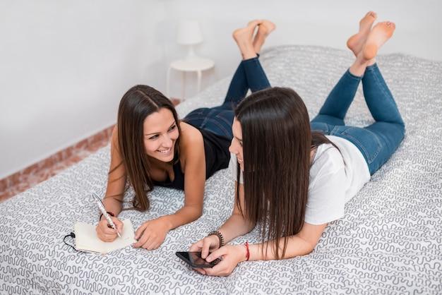 Souriant, jeunes femmes, coucher lit Photo gratuit