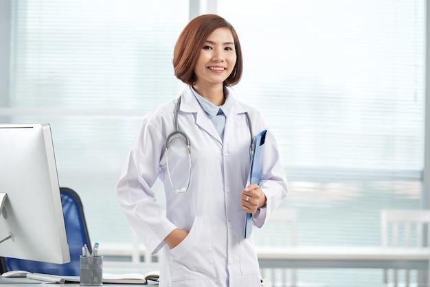 Souriant joli docteur debout dans le bureau de l'hôpital avec un dossier papier Photo gratuit