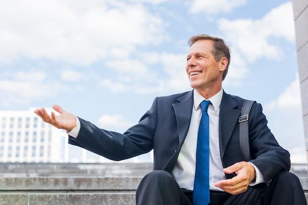 Souriant mature homme d'affaires assis sur l'escalier faisant le geste de la main Photo gratuit