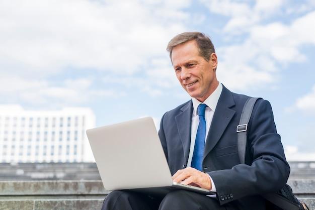 Souriant mature homme d'affaires utilisant un ordinateur portable à l'extérieur Photo gratuit