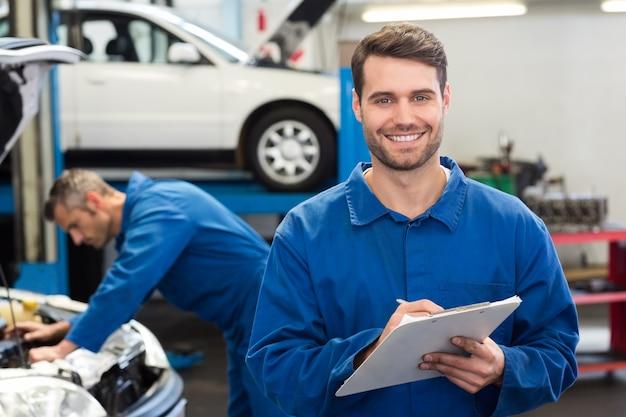 Souriant mécanicien écrit sur le presse-papiers Photo Premium