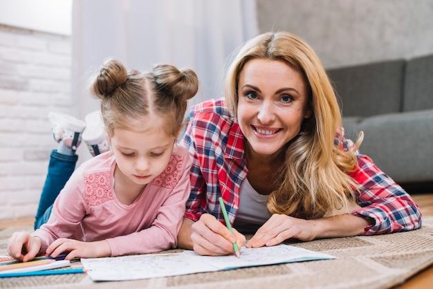 Souriant mère aidant à sa fille en dessin couché sur un tapis Photo gratuit