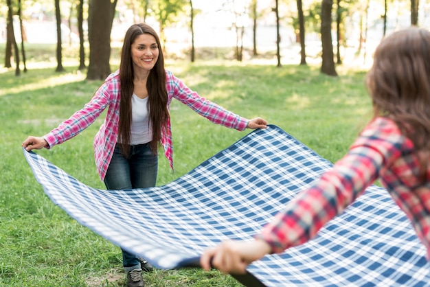 Souriant mère et fille plaçant une couverture damier bleu sur l'herbe verte Photo gratuit
