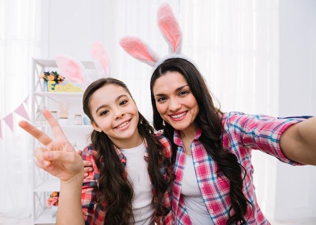 Souriant mère et fille portant des oreilles de lapin montrant le signe de la paix Photo gratuit