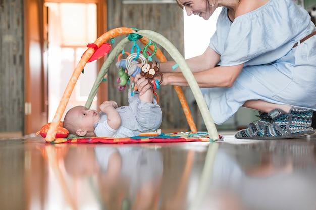 Souriant mère jouant avec son bébé allongé sur un tapis en développement sur le sol réfléchissant Photo gratuit