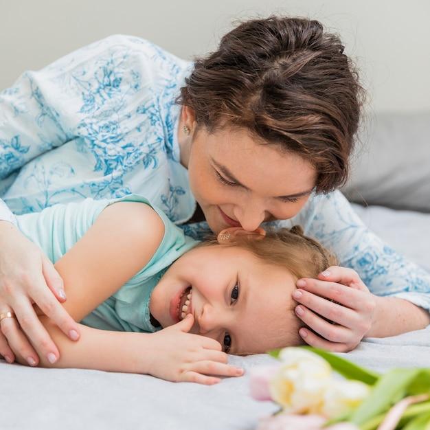 Souriant mère murmurant à l'oreille de sa petite fille sur le lit Photo gratuit
