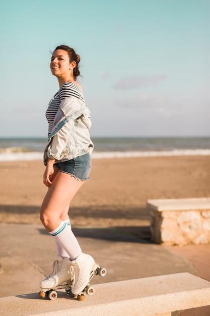 Souriant à la mode jeune femme debout sur un banc à la plage Photo gratuit