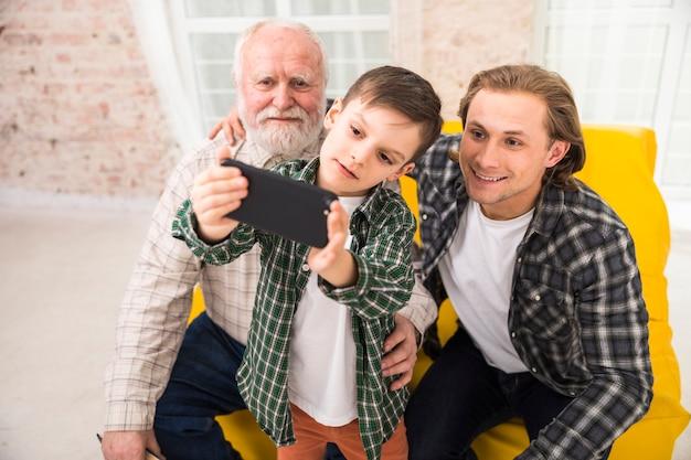 Souriant multi-génération famille prenant selfie avec smartphone Photo gratuit