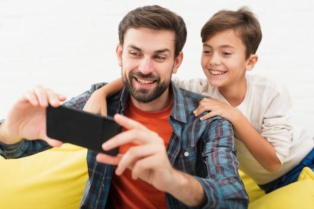 Souriant père et fils prenant des selfies Photo gratuit