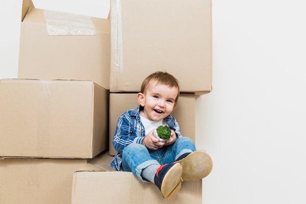 Souriant petit garçon assis sur la boîte en carton en mouvement tenant la plante de cactus Photo gratuit