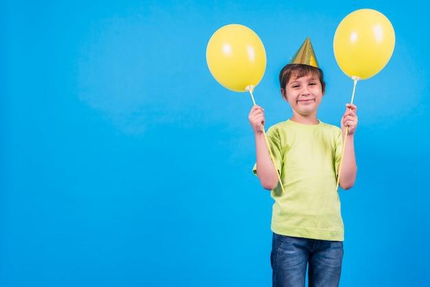 Souriant petit garçon tenant des ballons jaunes sur fond bleu avec espace copie pour le texte Photo gratuit