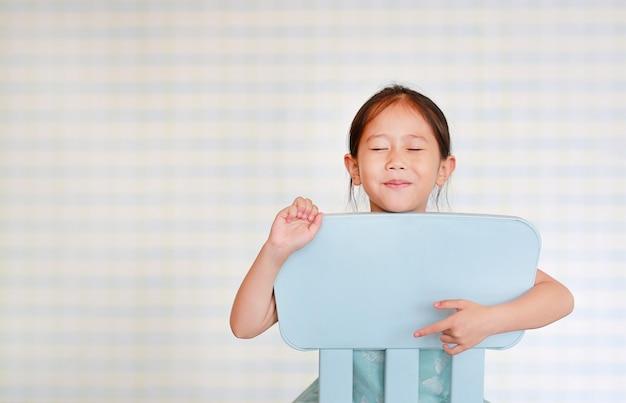 Souriant petite fille asiatique d'âge préscolaire dans une salle de jardin d'enfants pose sur une chaise en plastique Photo Premium