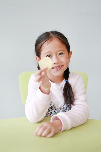 Souriant petite fille asiatique enfant mangeant des croustilles croustillantes sur blanc. Photo Premium