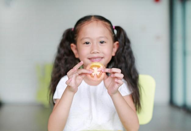 Souriant Petite Fille Enfant Asiatique Tenant Un Morceau De Tomate En Tranches. Kid Manger Concept D'aliments Sains. Focus Sur La Tomate Dans Les Mains Des Enfants. Photo Premium