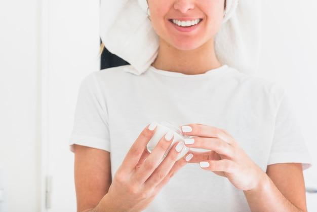 Souriant portrait de femme tenant une bouteille de crème hydratante dans les mains Photo gratuit