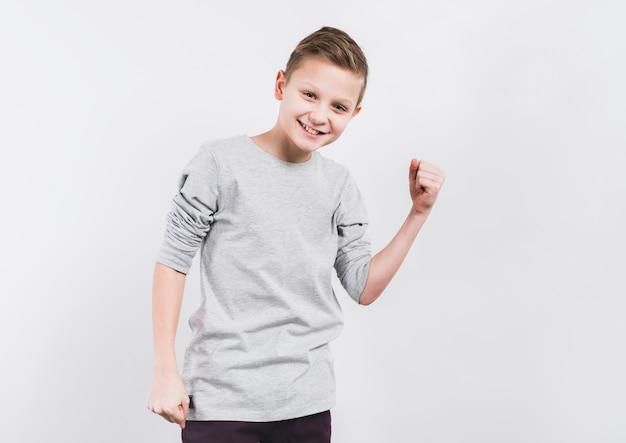 Souriant Portrait D'un Garçon Serrant Son Poing Debout Contre Un Fond Blanc Photo gratuit