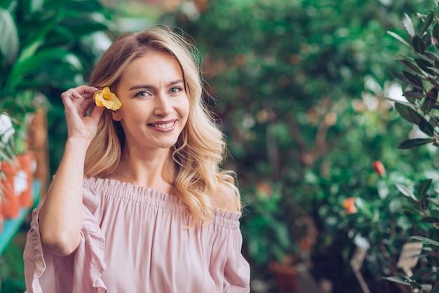 Souriant portrait de jeune femme blonde tenant une fleur jaune dans son oreille Photo gratuit
