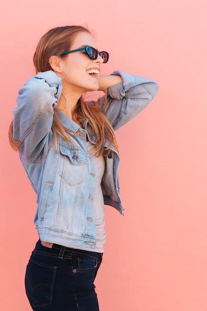 Souriant Portrait D'une Jeune Femme Portant Des Lunettes De Soleil Sur Fond Rose Photo gratuit