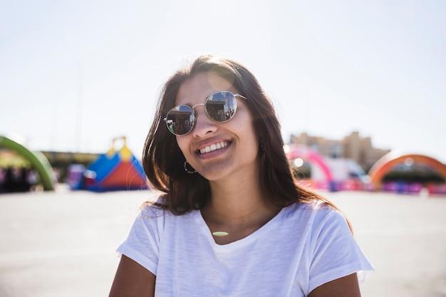 Souriant portrait d'une jeune femme portant des lunettes de soleil en regardant la caméra Photo gratuit