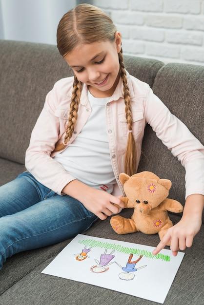 Souriant portrait d'une jeune fille assise sur un canapé, montrant la famille en train de dessiner pour ours en peluche Photo gratuit