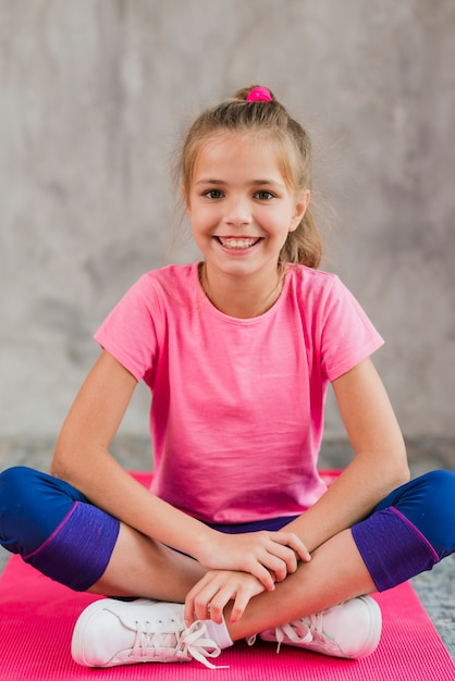 Souriant portrait d'une jeune fille assise sur un tapis rose contre un mur de béton gris Photo gratuit