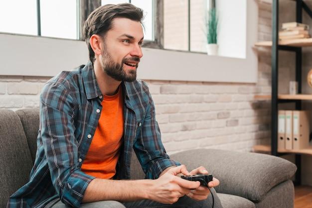 Souriant portrait d'un jeune homme assis sur un canapé jouant au jeu vidéo Photo gratuit
