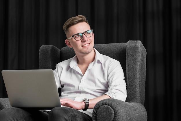Souriant portrait d'un jeune homme assis sur un fauteuil à l'aide de tablette numérique à la recherche de suite Photo gratuit