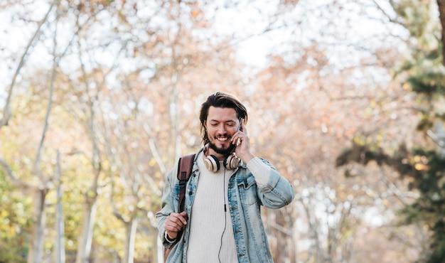 Souriant portrait d'un jeune homme marchant avec son sac à dos parlant au téléphone portable dans le parc Photo gratuit