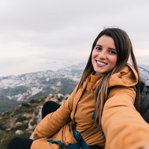 Souriant Portrait D'une Jeune Randonneuse Prenant Selfie Assis Au Sommet De La Montagne Photo gratuit