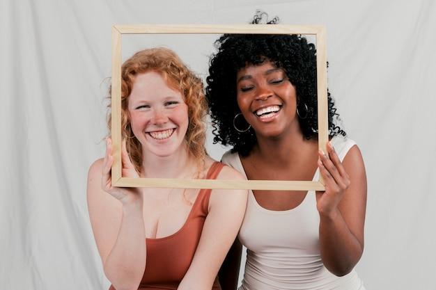 Souriant portrait de jeunes femmes africaines et blondes tenant un cadre en bois devant leur visage Photo gratuit