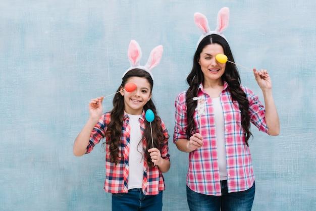 Souriant portrait d'une mère et fille couvrant un œil avec un accessoire d'oeuf de pâques Photo gratuit