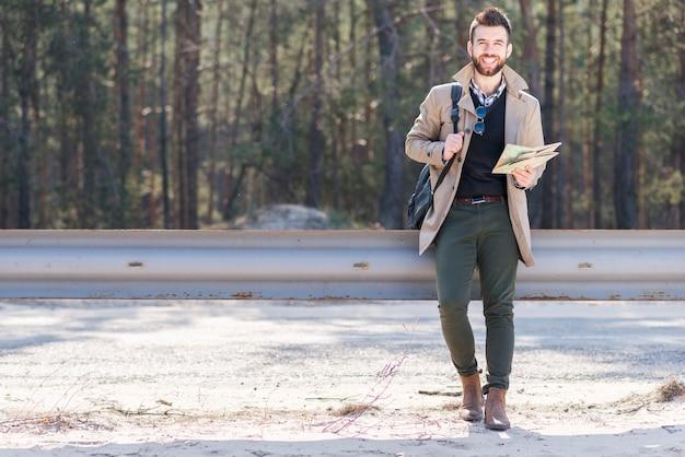 Souriant portrait d'un voyageur mâle tenant son sac à dos et carte Photo gratuit