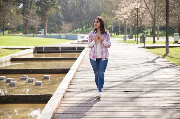 Souriant ravie jeune fille profitant du paysage dans le parc de la ville Photo gratuit