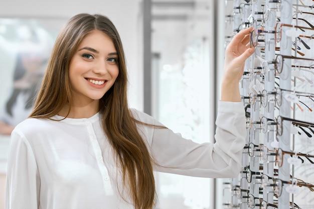 Souriant sympathique assistant optique dans un cabinet d'ophtalmologie. Photo Premium