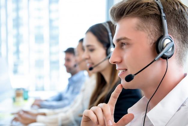 Souriant sympathique homme travaillant dans le centre d'appels avec l'équipe Photo Premium