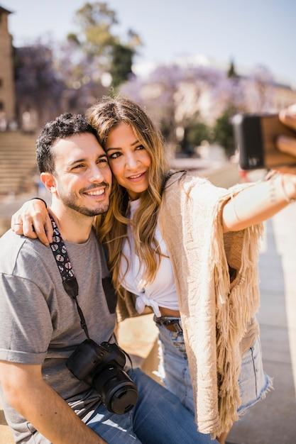 Souriant touristique prenant autoportrait sur téléphone portable Photo gratuit