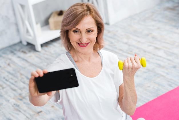 Souriant vieille femme avec des haltères prenant selfie à l'aide de téléphone portable Photo gratuit