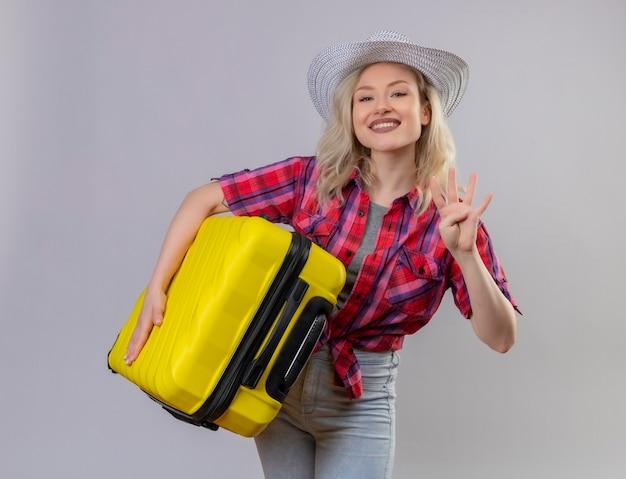 Souriant Voyageur Jeune Fille Portant Une Chemise Rouge Au Chapeau Tenant La Valise Montrant Quatre Sur Fond Blanc Isolé Photo gratuit