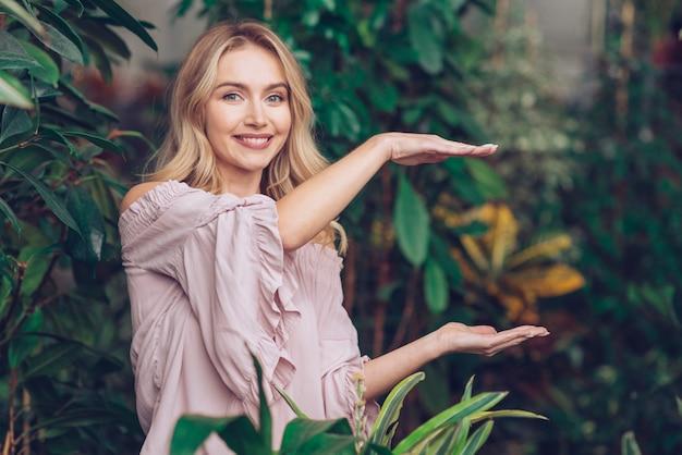 Souriante belle jeune femme montrant quelque chose sur les paumes de ses mains dans le jardin Photo gratuit