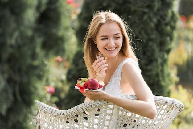 Souriante blonde jeune femme assise sur une chaise en mangeant des fruits dans le jardin Photo gratuit