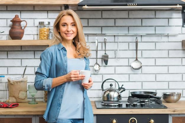 Souriante blonde jeune femme debout près de la cuisinière à gaz tenant une tasse à café blanche Photo gratuit