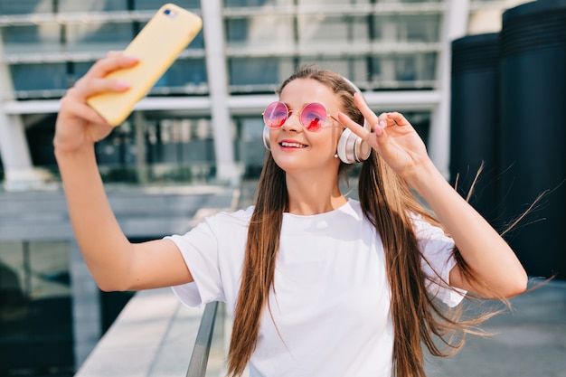 Souriante Et Dansante Jeune Femme Faisant Un Selfie Avec Son Smartphone Et écoute De La Musique Au Casque Photo gratuit