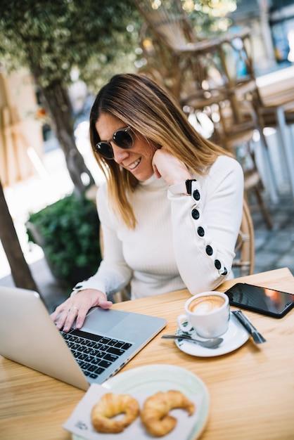 Souriante élégante jeune femme à l'aide d'un ordinateur portable à la table avec boisson et croissants au café de rue Photo gratuit