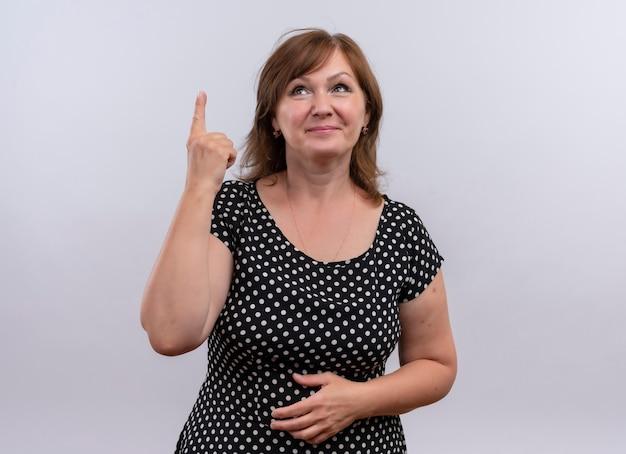 Souriante Femme D'âge Moyen Pointant Le Doigt Vers Le Haut Et Mettant La Main Sur Le Ventre Sur Un Mur Blanc Isolé Photo gratuit
