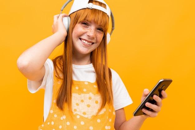 Souriante Fille Rousse Européenne Avec Un Casque Rouge Et Un Téléphone Photo Premium