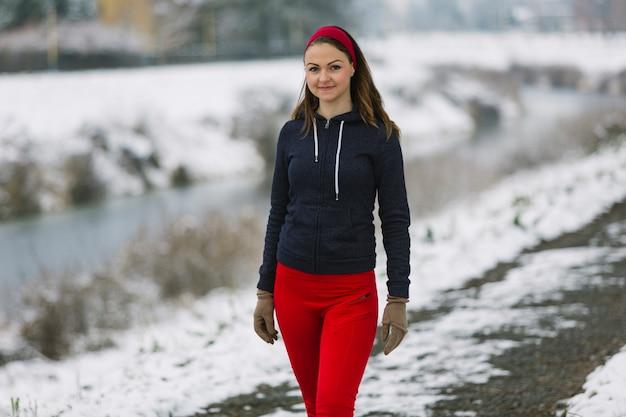 Souriante jeune athlète féminine debout en hiver Photo gratuit