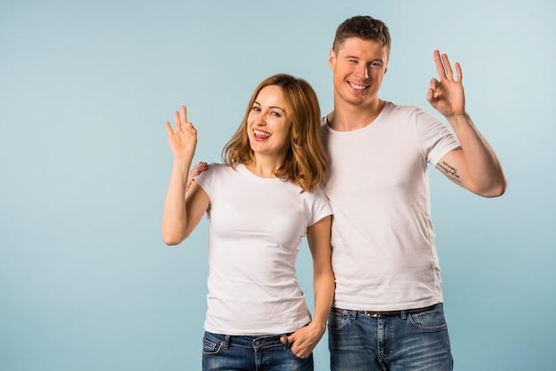 Souriante jeune couple montrant le geste de signe ok sur fond bleu Photo gratuit