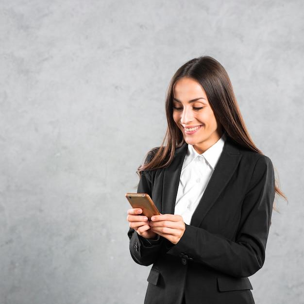 Souriante jeune femme d'affaires à l'aide de téléphone intelligent permanent sur fond de béton gris Photo gratuit
